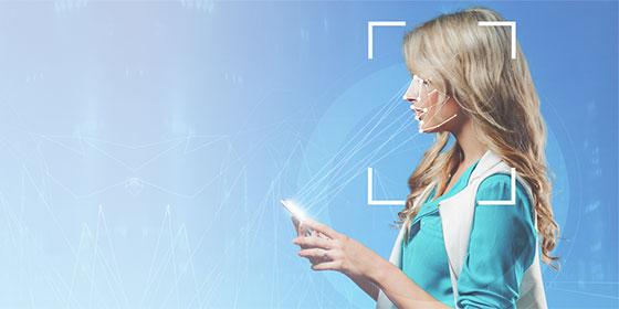 Mulher segurando o celular com o rosto sendo escaneado